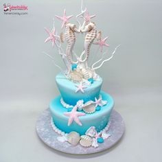 Mad hatter style wedding cake in an underwater scene decorated with two kissing seahorses made from pastillage.