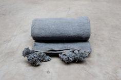 grey woollen blanket with pompoms