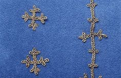 Embroidery, cross-shaped. Made of golden thread and originally fastened on textiles. Grave find, Björkö, Adelsö, Uppland, Sweden.SHM 34000:Bj 524