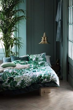A charming tropical vibe on this beautiful master bedroom with exotic leaves and patterns. An oriental pendant lamp completes the look.