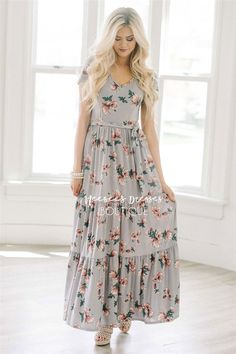 This beautiful maxi dress is unique and so comfortable! Dusty lilac full length dress features a pretty mauve floral print, short sleeves, elastic waist with tie sash and a tiered ruffle hem.