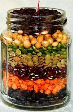 Um pote de vidro transparente Grãos : lentilha , arroz em casca , milho , feijão manteiga e grão de bico e amendoim . Folhas de...