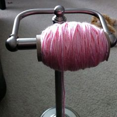 toilet paper holder with yarn next to the couch