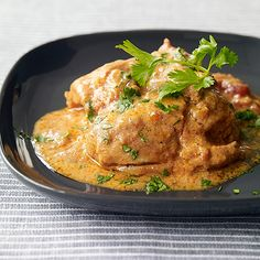 Slow Cooker Chicken Tikka Masala Recipe Main Dishes with crushed tomatoes, onions, minced garlic, ginger root, garam masala, dark brown sugar, ground cumin, ground coriander, boneless skinless chicken thighs, kosher salt, plain low fat greek yogurt, cilantro