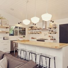 Rejuvenation's Rose City schoolhouse pendants + Halfway swing-arm sconces add inviting beams of light to this already brilliant kitchen renovation by Design Shop Interiors.
