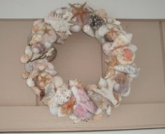 This is also easy and inexpensive to make.  I purchased a craft wreath from Michaels's and wrapped with cheesecloth (other gausy material can also be used.  I then hot glued my seashells that I had been collecting.  I also added them around the edges, covering all of the wreath except the back.  I purchased a round ring and sewed it to the back for hanging.  If you don't have any or enough seashells, they can be purchased at a craft store, like I did with the starfish.