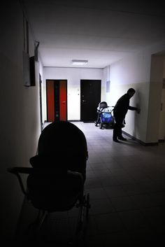 Aleksandros Katsis // A man leaves his son's stroller outside his apartment in a Soviet accommodation block.