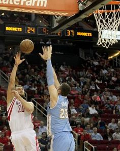 Rockets forward Donatas Motiejunas (20) shoots over Nuggets center Jusuf Nurkic (23) in the first half.