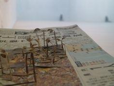 Hier neemt de natuur terug wat van haar was. de kunstenaar heeft uit een chinese krant een soort bonenstaakjes geknipt, die eruit steken.
