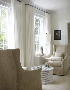 love this sitting area; the chair design; round ottoman; simple curtains; neutral palette