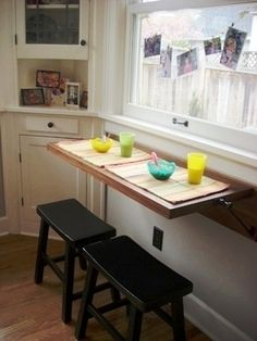 Love this solution for a tiny kitchen. Doubles as counter space and breakfast bar.