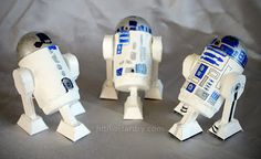 R2D2s made using popsicle sticks, a cardboard toilet roll tube, the bottom part of one of those plastic easter eggs used for egg hunts, the lid off a gallon milk jug, and a cardboard print out