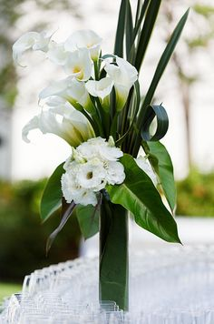 Centerpiece of gorgeous white calla lilies + lisianthus in a tall vase wrapped in green leaf.
