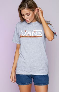 It's time to level up and take your gamer game, to the next level with this Vans X Nintendo Mario Short Sleeve Tee Grey! Featuring a short sleeve box print with a crewneck style, it displays the classic Nintendo characters through the VANS Logo print, along with a little VANS Nintendo print on the sleeve. Pair this look with some denim shorts and sneakers for a game winning cool casual look!   FABRICATION: 90% Cotton, 10% Polyester  SIZE & FIT: Measures 68cm from shoulder to hem Model's…