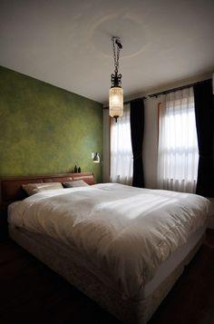寝室の壁には、手描きならではのニュアンスのあるグリーンのペイントが施されている。