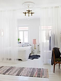 HATE that chandelier, but the sheer curtain to divide up a huge master bedroom is a great idea.