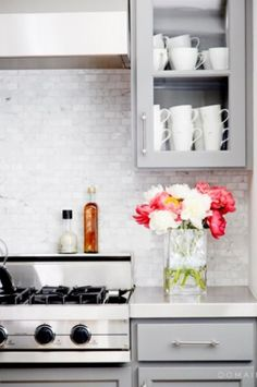 Gray Cabinetry With Marble Back Splash.