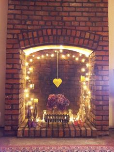 05 A Fireplace With String Lights A Hanging Heart And Some Candles For A Cute Look - Home Decor & Design Fireplace Filler, Empty Fireplace Ideas, Unused Fireplace, Hanging Fireplace, Fireplace Lighting, Candles In Fireplace, Fake Fireplace, Fireplace Design, Fireplace Mantels