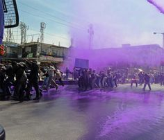 Kashmiri government employees shout anti government slogans as Indian police spray purple colored water to disperse a protest in Srinagar on April 17, 2012. Indian police detained dozens of government employees, used water cannons and resorted to baton charging the employees during the protest. The government employees were demanding an increase in the retirement age from 58 to 60 and the release of arrears.