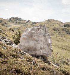 Le studio de design Bureau A a créé cette cabane installée dans un champs sur le flanc d'une montagne des Alpes suisses qui ressemble à un gros rocher de l'extérieur mais dont l'intérieur en bois est chaleureux et accueillant.