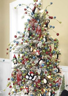 Snow flocked green tree covered with whimsical animal ornaments, multicolored glittered balls in red, blue, and green. Glitted ball garland in red, green and blue. New multicolor Sparkle Berry Sprays add to the Christmas whimsey!