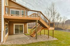 Custom designed cedar deck with u-shaped stairs and landing returning to concrete patio