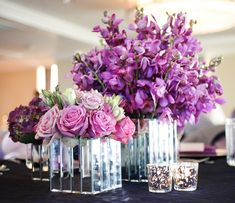 Purple orchids, roses and hydrangeas in mirrored square vases