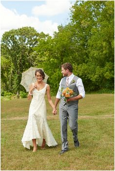 Groom holds his brides boquet as they take a walk with the bride carrying a white laced parisol at Hope Glen Farm Wedding