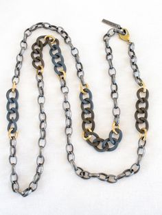"""Chunky links magically mixed into a pattern of vintage brass, our signature slate grey chain, and antique silver links. May be worn as a long, doubled, or tripled necklace, and as a bracelet. 56"""""""