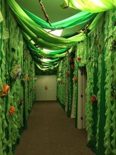 finished hallway for Journey off the map- We used green plastic tablecloths, tissue paper flowers, and homemade jungle vines.Our finished hallway for Journey off the map- We used green plastic tablecloths, tissue paper flowers, and homemade jungle vines. Jungle Theme Parties, Safari Theme, Jungle Safari, Jungle Theme Decorations, Camping Decorations, Green Party Decorations, Room Decorations, Off The Map, Imagination Station