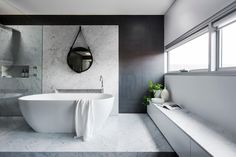 The bathing zone, defined by the use of Carrera marble, has the shower and bath raised on a platform.