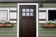 Dark door contrasts nicely with the siding and trim - Vintage by Tiny Heirloom