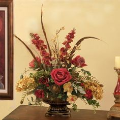 """Burgundy and Moss Silk Floral Design  makes a great centerpiece for a dining table.  Our popular embossed vase is overflowing with ivy, silk roses, snapdragons, silk orchids and hydrangea. Pheasant feathers are added for a finished touch. 25""""H x 24 """"W    Most of our beautiful silk flower arrangements can be customized to match your home. We can alter the size, color combination, types of silk flowers, and vase."""