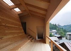 A wooden floor that curves up to become a wallallows light and airto flow throughthisbathhouse by Japanese studio Kubo Tsushima Architects