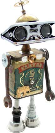 "Name: Jungle Boogie  D.O.B.: 11/26/11  Height: 12.5""  Principal Components: Tea tin, opera glasses, telephone ringer bell, wrenches, clock gear, hydraulic fittings, button.  Amy Flynn Designs."