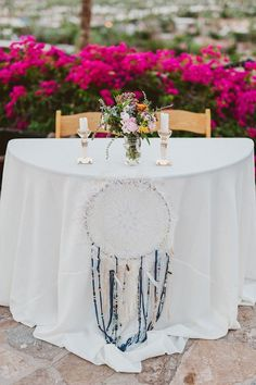 Hang an ornate dreamcatcher accompanied by a mini centerpiece for a boho chic vibe.