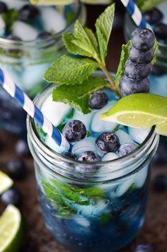 Blueberry Mojito - 1 cup fresh blueberries (plus extra for garnish), 4 oz clear rum, 10 fresh mint leaves, 2 teaspoons sugar, juice of 2 limes, 6 oz club soda, ice