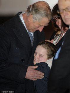 Emotional: Prince Charles receives a hug from Megan Faulds, 8, the granddaughter of survivor Ann Faulds