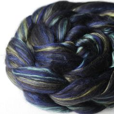 Inspired by black opals, this blended top was designed by HipStrings and custom made for our shop by a UK mill. It features 37.5% dyed 23 micron merino, 25% Mulberry Silk, 25% Black baby alpaca and 12.5% Bamboo.  Care: Handwash. Lay flat to dry. This fiber will felt!  Picture is representative of the fiber and all efforts have been made to reproduce the colors accurately - color may vary according to your monitor.