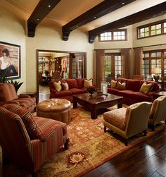 This living room resembles a Tuscan style design. The coffee table has bulky legs, and the chairs and sofas are a Lawson style. The wooden beams on the ceiling are also elements typically seen in Tuscan designs.