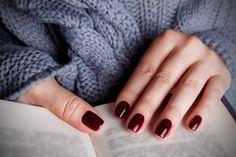 Winna czerwień, przypominająca swoim odcieniem dojrzałe wiśnie lub czerwone wino, idealnie komponuje się z opatulającymi, ciepłymi swetrami, które nosimy jesienią. Przy ciemnych kolorach lepiej postawić na krótsze paznokcie. Kontrast nasyconej czerwieni i szarych ubrań tworzy wyjątkowo zgrany duet.