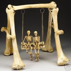Miniature swing set made of bones, with two skeletons side by side in the swing.
