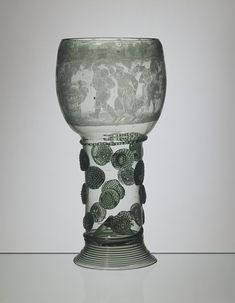"""1650-1700 Dutch Wine glass at the Victoria and Albert Museum, London - From the curators' comments: """"The 'roemer' was the most popular drinking glass for white wine in the seventeenth-century Netherlands. A roemer is made out of green glass and consists of a foot, a hollow shaft, decorated with prunts, and a bowl. Bowl and shaft are blown as one hollow shape and visually separated with a ribbed glass thread around the outside. The prunts on the shaft are decorative but also provide a good…"""