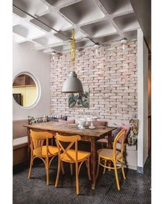 O arquiteto Maicon Antonioli multiplicou o espaço de refeições desta cozinha ao propor um banco embutido em L num dos cantos do ambiente. Ao fundo, o ar rústico da mesa de madeira de demolição é reforçado pela parede de tijolos da Cia das Telhas. Cadeiras amarelas da Isto É Brasil. Almofadas estampadas Quaker Decor. Lustre Yamamura. Foto Marco Antonio/Editora Globo #acaradecasaejardim #cozinha #kitchen #decoration #cozy Dining Chairs, Dining Room, Dining Table, Outdoor Tables, Outdoor Decor, Outdoor Furniture, Mirror, Kitchen, Instagram Posts