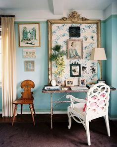 An office space with a white loop chair and an inspiration board with a floral pattern.