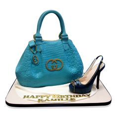 Blue Gucci Bag And Shoe Cake  Designer hand bags and stiletto shoes are all the rage and Kamille is a lady with style and class! This cake was ordered for her on the occasion of her Birthday.  We were told that she loves blue and gold and we created this stunning cake for her.  The base is a square of cream fondant surrounded by a black ribbon.  http://cmnycakes.com/gallery2/v/Cakes+For+All+Occasions/Blue+Gucci+Bag+And+Stiletto+Cake.html