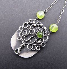 This necklace has been made using silver wire combined with silver sheet. The wire-wrapping technique is complimented with the faceted peridot that is nested in the silver bezel.