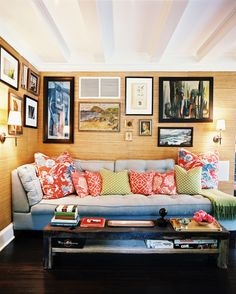 Grass-cloth-covered walls hung with art and a blue couch in a family space  Details: Beige Eclectic-Traditional Living Room, Beige Traditional-Tropical Wall Treatment, Multicolored Asian-Vintage Decor  Keywords: David Cafiero, Rustic Coffee Table, Gallery Wall, Ceiling Beams, Blue Couch, June July 2010 Issue, Throw Pillows, Oil Painting, Hamptons, Grasscloth Wallpaper  (Source: Lonny)