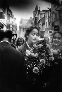 A young woman with a big bunch of roses on the Rue De La Republique in May 1986 in Saint Denis, France. Photo by Robert Doisneau