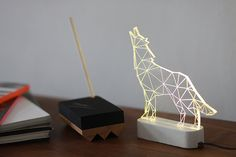 Beautiful modern howling wolf lamp, laser engraved woodland themed decorative lamp.  Add modern simplicity and humour to your house or office with this handmade wolf lamp. Comes with a grey or white coloured base. The lamp comes with on/off clicker and cord, fits standards worldwide 100v-240v - EU plug. Customers from the US will require a standard issue adapter. Lit by hidden LEDs, it will brighten any space while keeping your electricity bills down to a minimum.  Height : 18 cm = 6 Base…